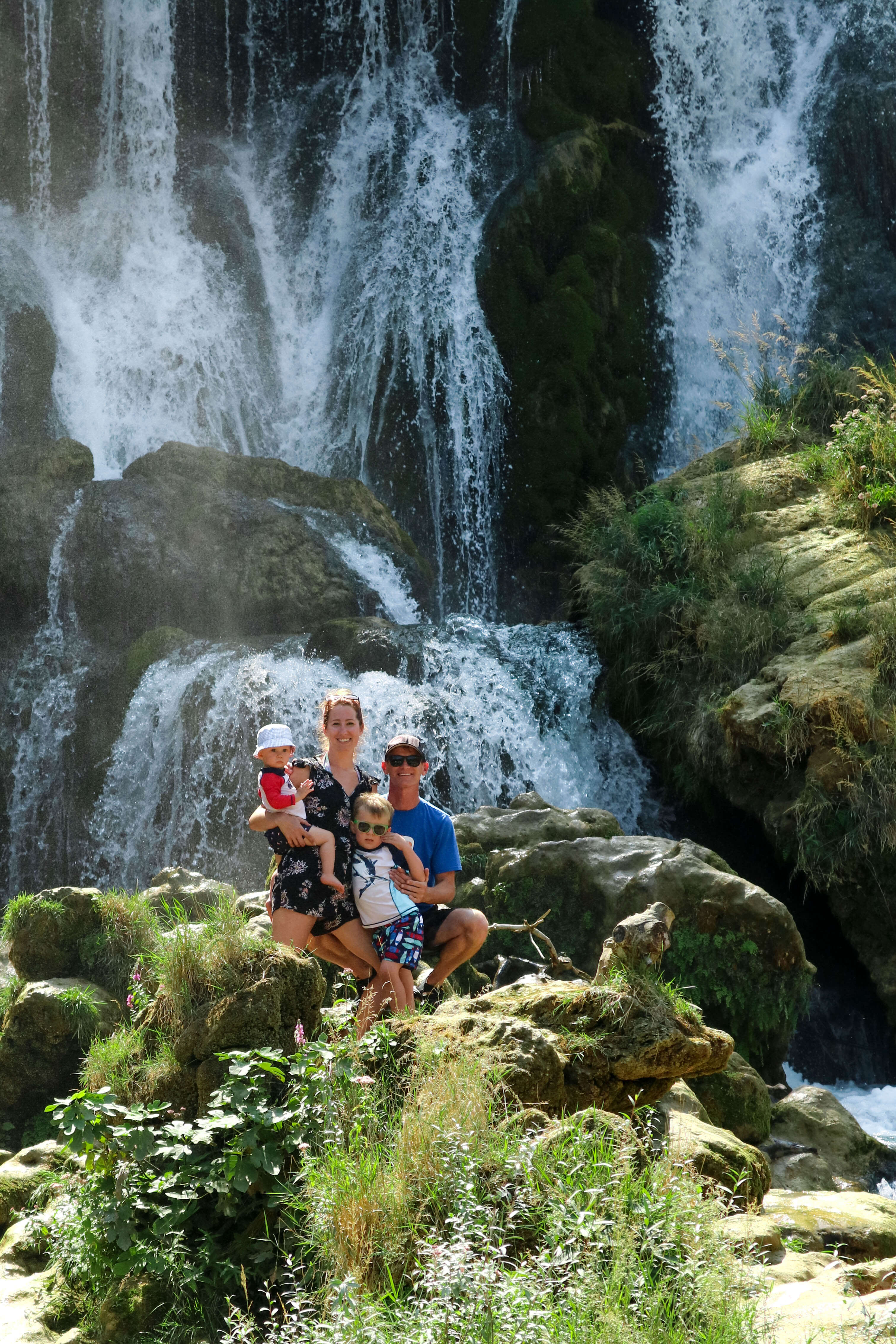 Family posing in front of a waterfall at Kravice Falls