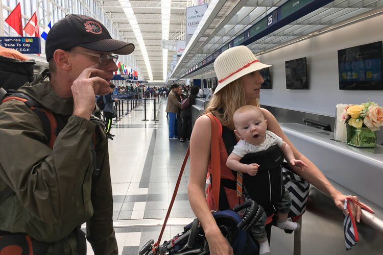 Kristin, Andrew, and Benjamin wait in line at the airport with the umbrella stroller and yoga strap