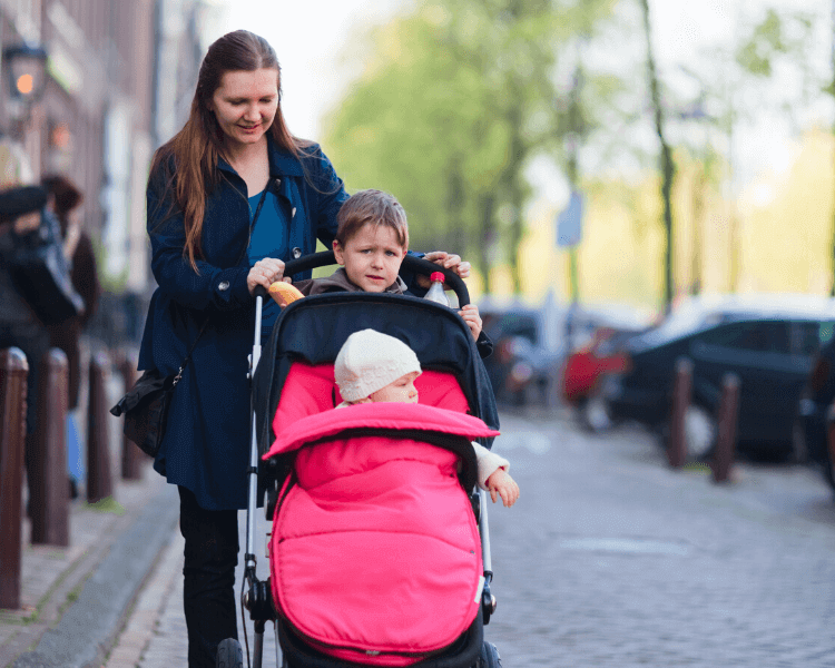 woman with children in a sit and stand stroller on a city street