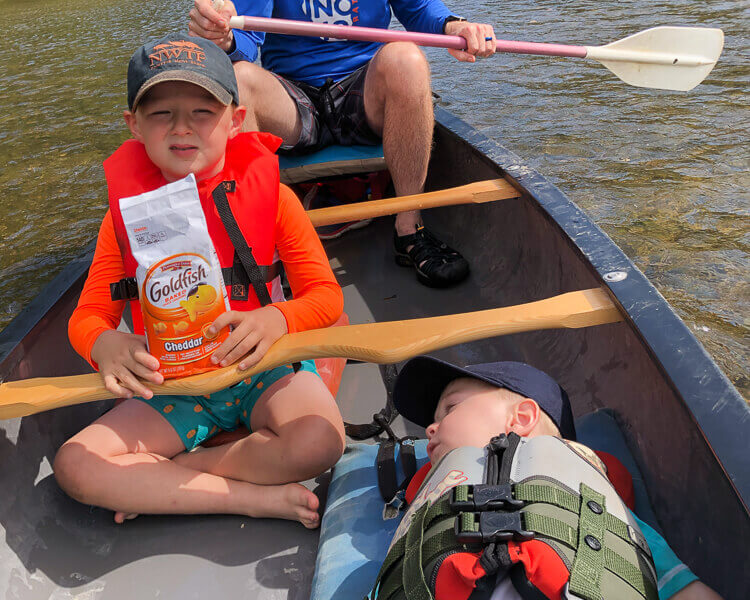 kids snacking and napping in canoe