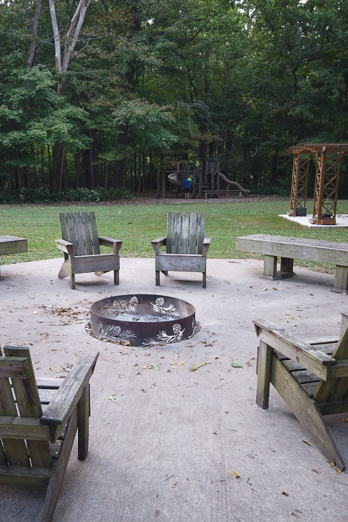 chairs around a fire pit with playground in the background at Turkey Run Inn and Cabins